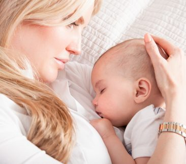Blond woman lying beside a baby
